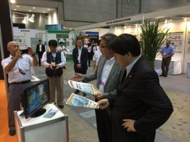JIRCASブースにおいて、齋藤プログラムディレクターの説明を受ける林農林水産大臣