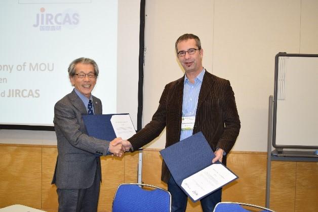 写真2 署名済み文書を持ち握手を交わす岩永理事長とiEES-ParisのLata氏