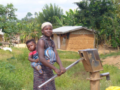 水へのアクセス (Mother with child drawing well water by hand pump installed in the village)