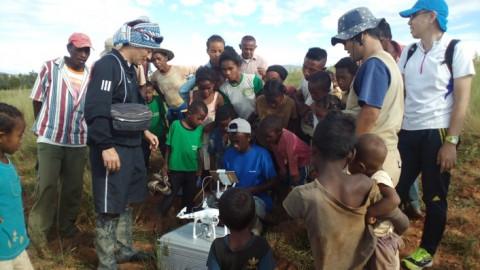 ドローンでの現地水田調査とそれを見守る農家の人々